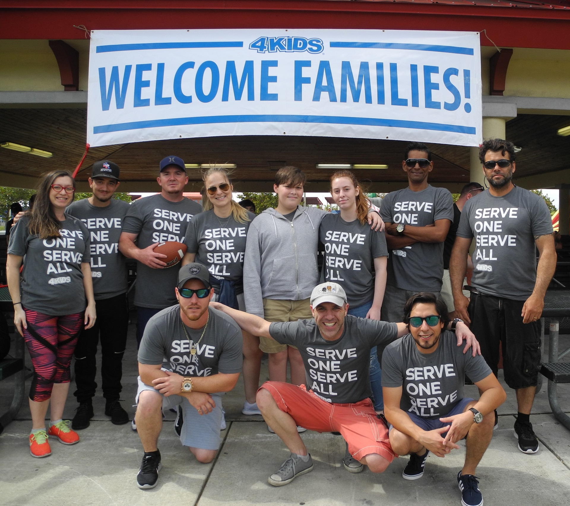 4 Kids Barbecue with employees posing under welcome families sign